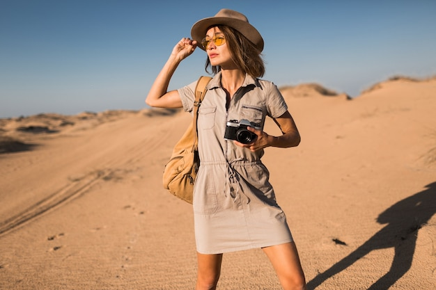 Stijlvolle jonge vrouw in kaki jurk wandelen in de woestijn, reizen in afrika op safari, hoed en rugzak dragen, foto nemen op vintage camera