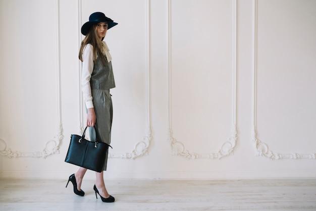 Stijlvolle jonge vrouw in kostuum en hoed met handtas in de kamer
