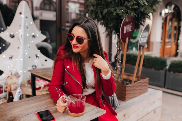Stijlvolle jonge vrouw in rode kledij zittend aan tafel met een kopje thee en telefoon erop