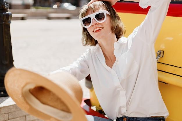 Stijlvolle jonge vrouw in witte zonnebril gekleed in wit overhemd en spijkerbroek met een strohoed in haar hand zit op de bumper van een felrode en gele minivan.