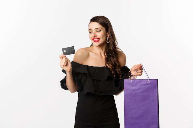 Stijlvolle jonge vrouw in zwarte jurk gaan winkelen, met tas en creditcard, glimlachend tevreden, staande op witte achtergrond.