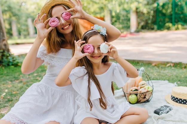 Stijlvolle jonge vrouw kwam met mooie dochter om te parkeren om samen een weekend door te brengen. outdoor portret van bruinharige meisje een grapje met moeder tijdens het eten van koekjes op deken.