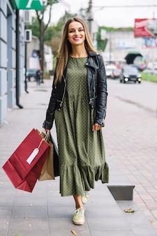 Stijlvolle jonge vrouw lopen met kleurrijke boodschappentassen op straat