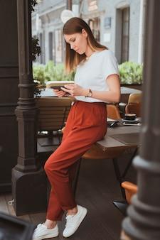 Stijlvolle jonge vrouw met digitale tablet die in straatcafé werkt
