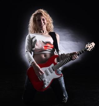 Stijlvolle jonge vrouw met een gitaar die een rocknummer uitvoert. geïsoleerd op een donkere