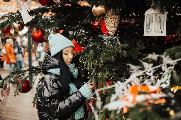 Stijlvolle jonge vrouw met in modieuze gebreide muts en sjaal in de stad in de buurt van de kerstboom