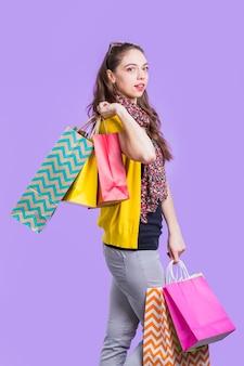Stijlvolle jonge vrouw met kleurrijke papieren zak