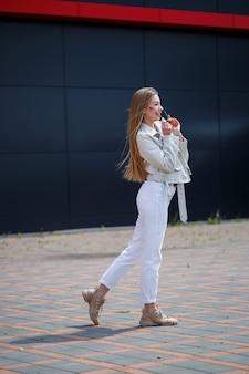 Stijlvolle jonge vrouw met lang blond haar van europese uitstraling met een glimlach op haar gezicht. meisje in een witte jas en witte spijkerbroek een warme zonnige zomerdag op een achtergrond van een grijs gebouw