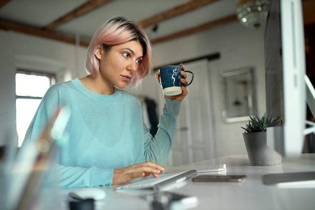 Stijlvolle jonge vrouw met roze haren zittend op haar werkplek te typen op het toetsenbord, het drinken van thee gebruiken