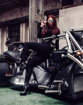 Stijlvolle jonge vrouw model poseren op een motorfiets tentoonstelling.
