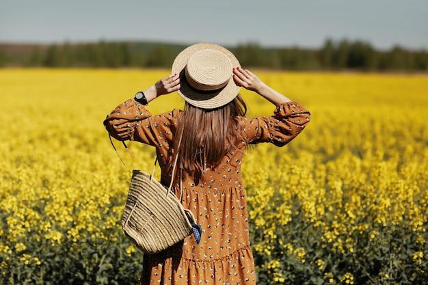 Stijlvolle jonge vrouw op een gebied van gele bloemen. meisje in strohoed en in een gebloemde jurk en met een rieten tas.