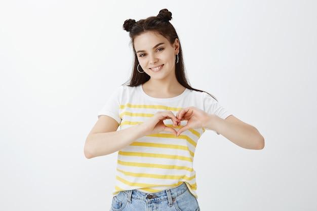 Stijlvolle jonge vrouw poseren tegen witte muur