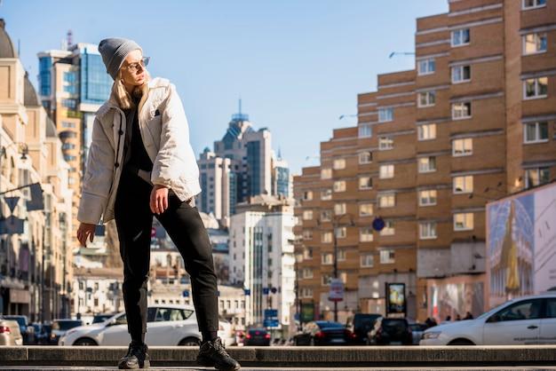 Stijlvolle jonge vrouw poseren voor gebouwen van de stad