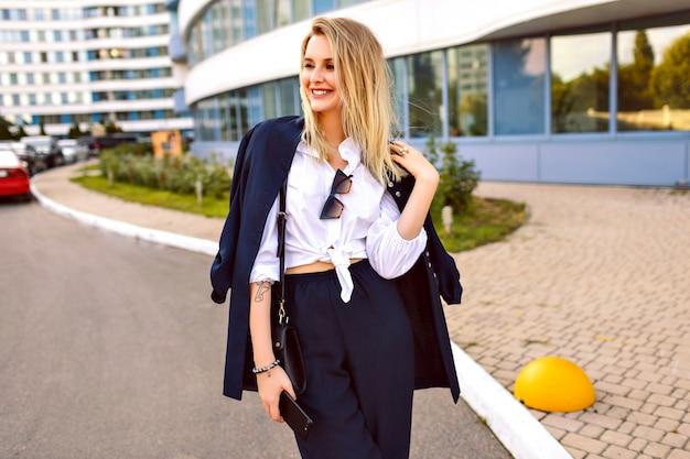 Stijlvolle jonge vrouw trendy marine pak dragen, poseren in de buurt van moderne gebouwen, modieuze accessoires, glimlachend einde genieten van vrije zonnige zomerdag, wandelen in de buurt van kantoor.