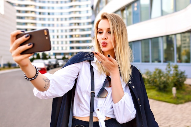 Stijlvolle jonge vrouw trendy marine pak dragen, poseren in de buurt van moderne gebouwen, modieuze accessoires, selfie maken en luchtkus naar u verzenden, positieve stemming.