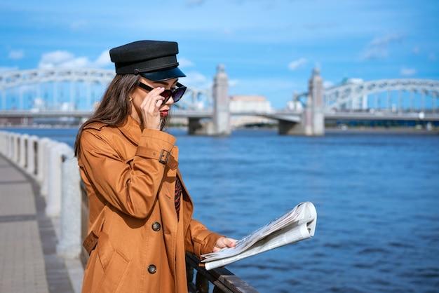 Stijlvolle jonge vrouw van kaukasische etniciteit leest verse krant in zonnebril en zwarte pet mooie bruine jas staande aan de kade van de rivier op zonnige dag