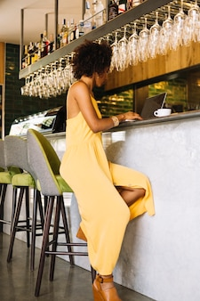 Stijlvolle jonge vrouw zitten in de buurt van de bar met behulp van laptop