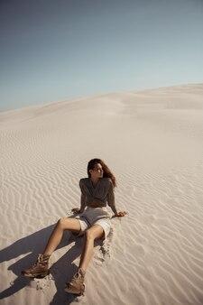 Stijlvolle jonge vrouw zitten in de woestijn reizen in afrika warme zomerdag zonnig weer mooi