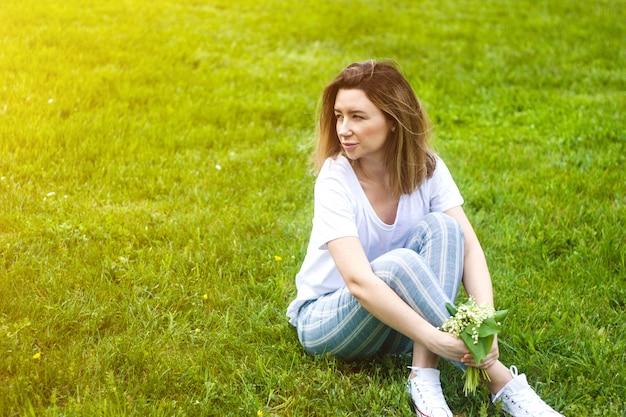 Stijlvolle jonge vrouw zittend op groen gras in zonnige warme dag