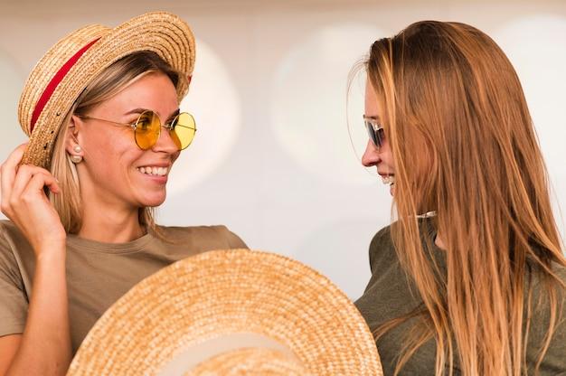 Stijlvolle jonge vrouwen die bij elkaar glimlachen