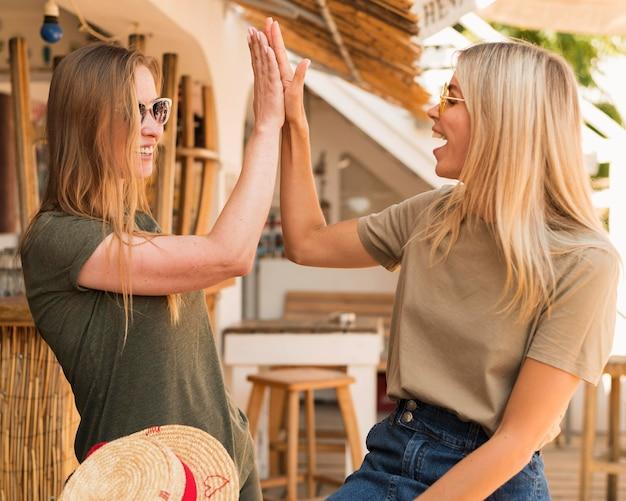 Stijlvolle jonge vrouwen die blij zijn elkaar te zien