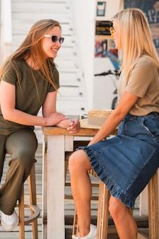 Stijlvolle jonge vrouwen die met elkaar praten