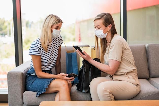 Stijlvolle jonge vrouwen die mobiele telefoon doorbladeren