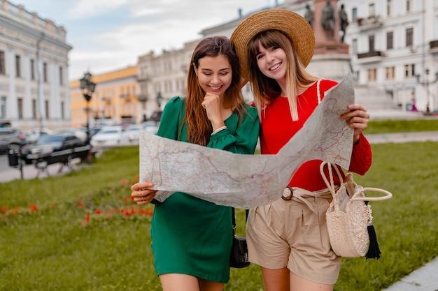 Stijlvolle jonge vrouwen die samen reizen, gekleed in trendy lente-outfit en accessoires die plezier hebben met het vasthouden van de kaart
