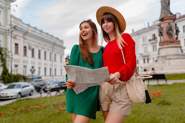 Stijlvolle jonge vrouwen die samen reizen in europa, gekleed in trendy lente-outfits en accessoires
