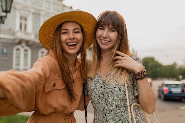 Stijlvolle jonge vrouwen die samen reizen in europa, gekleed in trendy lentejurken en accessoires