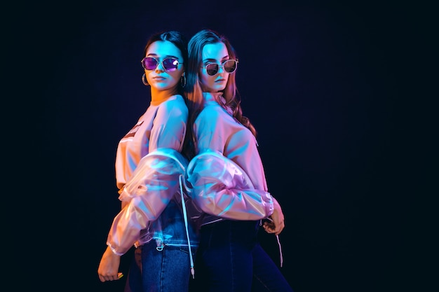 Stijlvolle jonge vrouwen die zich voordeed in neonlicht