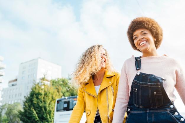 Stijlvolle jonge vrouwen met vriendelijke bijeenkomst wandelen in de straat. lgtb-concept