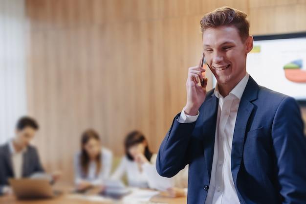 Stijlvolle jonge zakenman draagt een jas en shirt op de achtergrond van een werkbureau met mensen praten op een mobiele telefoon