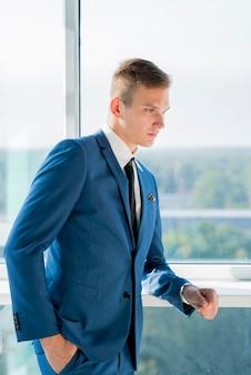 Stijlvolle jonge zakenman poseren in de buurt van het venster