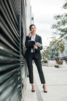 Stijlvolle jonge zakenvrouw praten over mobiele telefoon map in de hand te houden