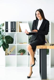 Stijlvolle jonge zakenvrouw zittend op een bureau met behulp van laptop