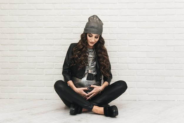 Stijlvolle jonge zwangere meisje in zwarte kleding met krullen op witte muur. foto's wachten op baby