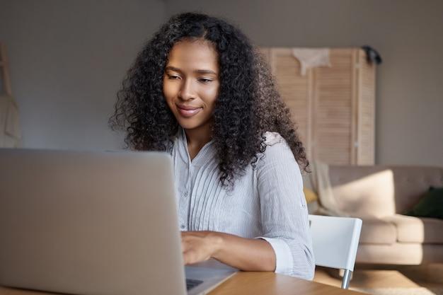 Stijlvolle jonge zwarte vrouw met krullend haar met behulp van laptop voor extern werk. schattig afrikaans meisje op zoek naar informatie op internet, thuis genieten van een snelle draadloze verbinding op electroni cgadget
