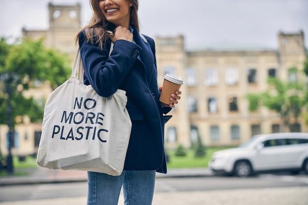 Stijlvolle jongedame die lacht terwijl ze in de buurt van gebouw staat met tas en kopje koffie in handen