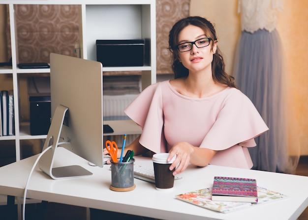Stijlvolle jongedame in roze luxe jurk werken op kantoor op computer