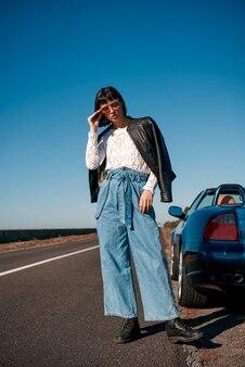 Stijlvolle jongedame in zonnebril met een kapsel in de buurt van een auto zonder dak
