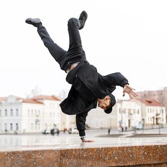 Stijlvolle jongeman danser in zwarte spijkerbroek in een stijlvol jasje met een pet in zonnebril doet een handstand in de stad op straat. amerikaanse hipster.