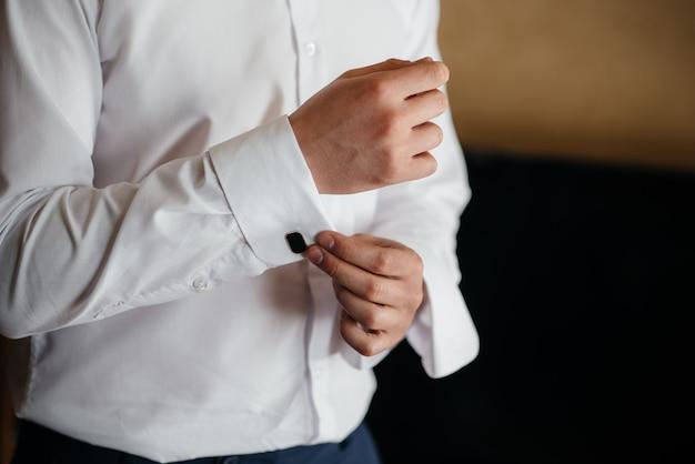Stijlvolle jongeman die de manchetknopen op de mouwen dichtknoopt. stijl