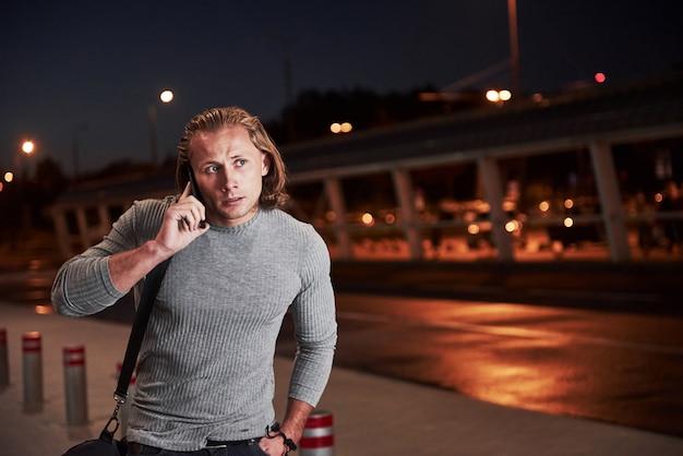 Stijlvolle jongeman die door de nachtstraat in de buurt van de weg loopt en een gesprek voert aan de telefoon