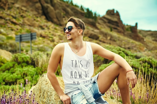 Stijlvolle jongeman in casual hipster kleding die zich voordeed op de natuur