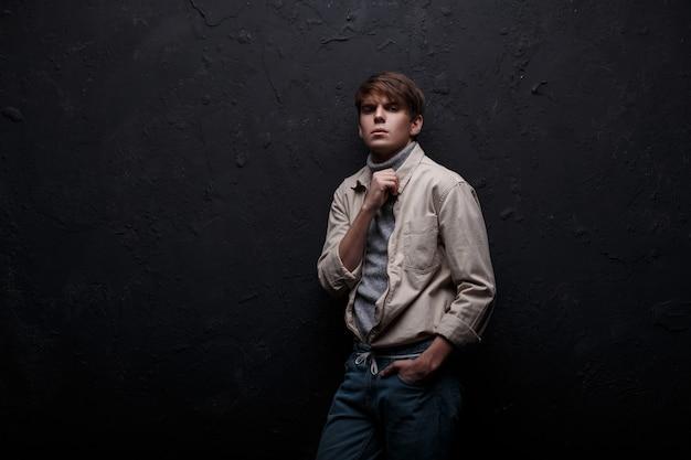 Stijlvolle jongeman in een modieus modern jasje in een grijze trui met een modieus kapsel in vintage spijkerbroek poseren in een studio in de buurt van een zwarte muur. knappe modieuze kerel. amerikaanse jongen