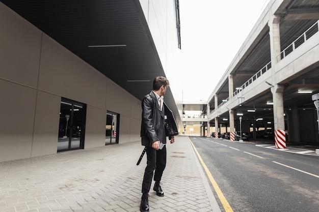 Stijlvolle jongeman in een oversized leren jas in vintage broek in coole laarzen met een modieuze zwarte rugzak loopt op straat in de buurt van de parkeerplaats. moderne coole kerel in trendy kleding buitenshuis.