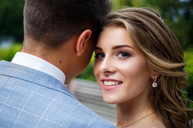 Stijlvolle jongeman in een pak de bruidegom en de bruid mooi meisje in een witte jurk met een treinwandeling in het park op hun trouwdag