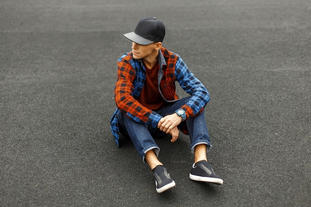 Stijlvolle jongeman in een zwarte pet, overhemd, spijkerbroek en sneakers zit op de stoep