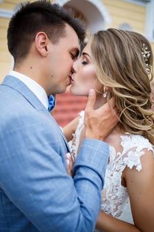 Stijlvolle jongeman in het kostuum van de bruidegom en de bruid mooi meisje in een witte jurk met een trein lopen op de achtergrond van een groot huis met kolommen op hun trouwdag Premium Foto